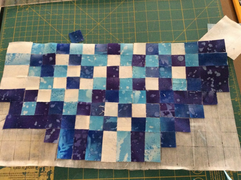 Arrange the fabric squares  on the sticky side of grid